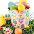 Easter bucket with colored eggs, candy and yellow chicks — Stock Photo #67721231