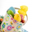 Easter bucket with colored eggs, candy and yellow chicks — Stock Photo #67721353