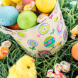 Easter bucket with colored eggs, candy and yellow chicks — Stock Photo #67721385