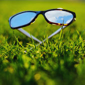 Sunglasses lying grass reflecting the blue sky — Stock Photo