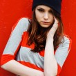 Portrait of a beautiful fashion girl in hat and striped sweater on a red wall outdoor — Stock Photo #54835317