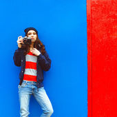 Portrait of a beautiful hipster girl with a camera on the background photon makes blue walls and red doors — Stock Photo