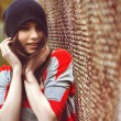 Portrait of a beautiful girl in a hipster hat and striped jacket  at the gate outdoor — Stock Photo #54914713