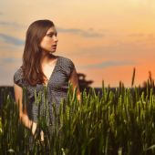 Young woman on field under sunset light — Stock Photo