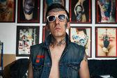 Tattoo artist in denim vest in studio — Stock Photo