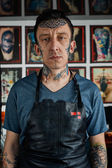 Tattooed guy in leather apron — Stock Photo