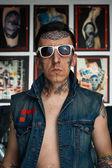 Tattooed man in denim vest and sunglasses — Stock Photo