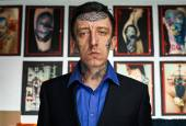Man with tattooes on face in black jacket and blue shirt — Stockfoto