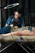 Tattoo artist makes a tattoo in studio — Stock Photo