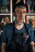 Tattooist in black leather apron in studio — Stock Photo