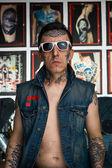 Tattoo master in denim vest and sunglasses in studio — Stock Photo