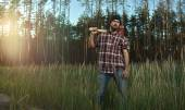 Bearded Lumberjack in Hat holding a big Axe on Shoulder in Fores — Stock Photo