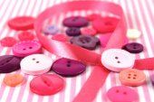 Pink and purple haberdashery buttons and craft ribbon — Stock Photo