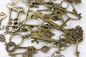 Pile of antique brass keys on a distressed wood background. — Стоковое фото