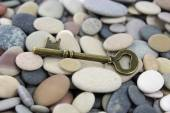 Antique old brass key on beach stones — Stock Photo