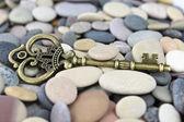 Old Brass key on a pebble beach — Stock Photo