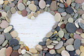 Heart shape made with pebbles on a white distressed wood backgro — Stock Photo