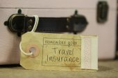 Travel insutance tag on vintage suitcase — Stockfoto