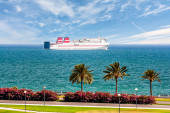 Passenger ship sails along the promenade with palm trees — Stock Photo