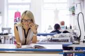 Self employed woman taking customer orders by phone — Stock Photo
