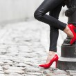 Woman wearing black leather pants and red high heel shoes in old town — Stock Photo #56060009