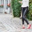 Woman wearing black leather pants and red high heel shoes in old town — Stock Photo #56060055