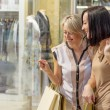 Two women looking through shop window — Stock Photo #56060741