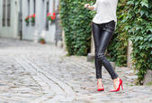 Woman wearing black leather pants and red high heel shoes in old town — Stock Photo