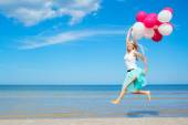 Happy woman holding balloons and jumping in the air — Stock Photo