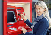 Happy woman using ATM to withdraw money — Stock Photo