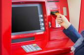 Woman inserting credit card into ATM to withdraw money — Stock Photo