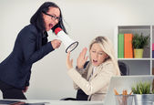 Mad boss shouting at employee on megaphone — Stock Photo