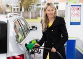 Young woman refilling car in gas station — Stock Photo