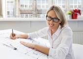 Young female architect sitting at her desk in the office — Stock Photo