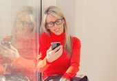 Young cheerful woman using smartphone — Stock Photo