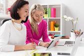 Två kvinnor tittar på Tablet PC: n medan arbetande i kontor — Stockfoto