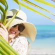 Woman with summer hat on the beach hiding behind palm leaf — Stock Photo #69980215