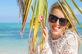 Cheerful woman behind palm leaf on the beach — Stock Photo