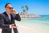 Businessman talking on phone at the beach — Stock Photo