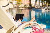 Woman using tablet computer on vacation in luxury resort — Stock Photo