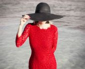 Woman in red dress and black hat — Stock Photo