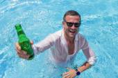 Young happy man partying in swimming pool — Stock Photo
