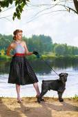 Beautiful girl with a Scottish Terrier in the Park — Stock Photo