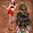 Girl in sexy suit of Santa Claus near the Christmas tree — Stock Photo #57793087