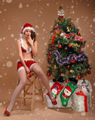 Girl in sexy suit of Santa Claus near the Christmas tree — Stockfoto