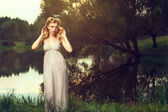 Thoughtful girl in a long sundress on the lake — Foto de Stock