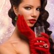 Isolated Glamour girl in red gloves holding a glass of champagne. — Photo #61251261