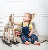 Little girl  surrounded by toys and holds a wooden horse — Stock fotografie