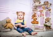 Little girl  sitting  surrounded by toys — Stock Photo