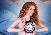 Beautiful woman holding a large clock. — Stock Photo
